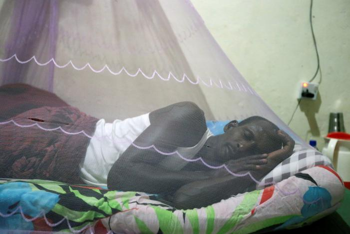 Khalif Dahir, 47, a driver at the Aamin Ambulance, sleeps inside a mosquito bed-net in his house after returning from duty, in Mogadishu