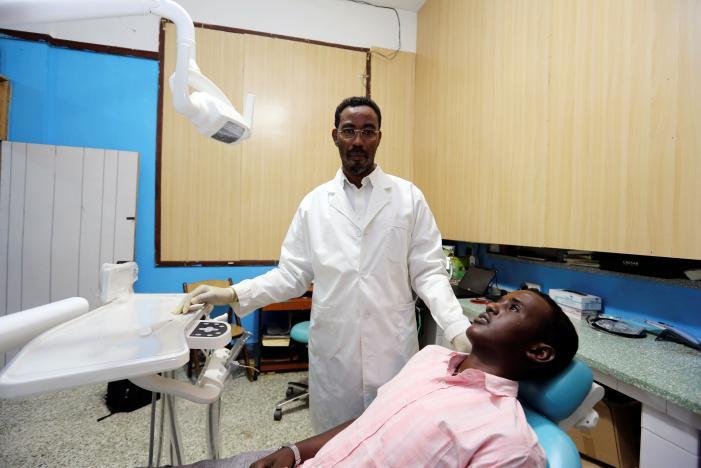 Somali dentist Dr. Abdulkadir Abdurrahman, the founder of Aamin Ambulance, prepares to treat a patient in his dental clinic in Banadir hospital in Mogadishu