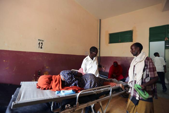 Khalif Dahir, a driver at the Aamin Ambulance, helps Faduma Hassan a diarrhea patient in Banadir hospital after transporting her from a camp for the internally displaced people on the outskirts of Mogadishu