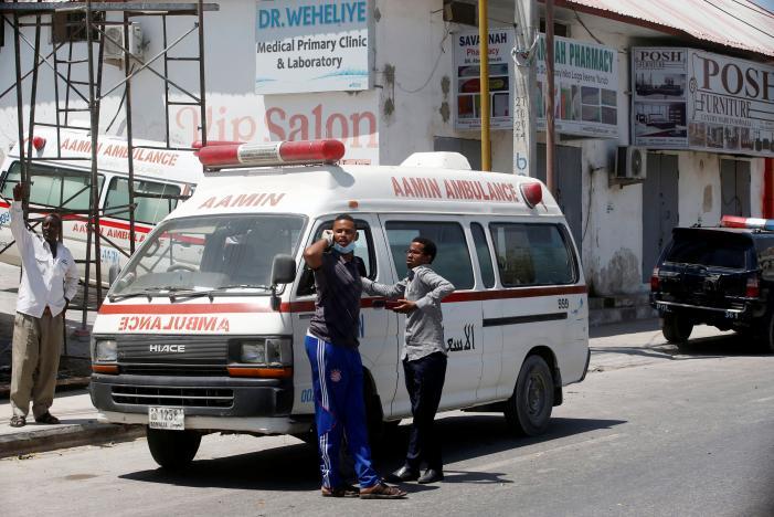 Aamin Ambulance staff are seen outside their ambulances near the scene of a suicide car explosion in Maka Al Mukarama street of Mogadishu
