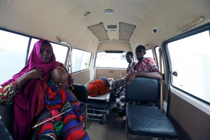 Relatives ride with Faduma Hassan, a diarrhea patient, inside the Amin Ambulance as they are transported to the Banadir hospital from a camp for the internally displaced people on the outskirts of  Mogadishu